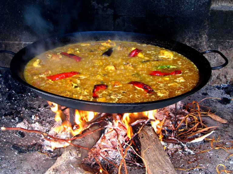 Paella being cooked as street food on an open fire